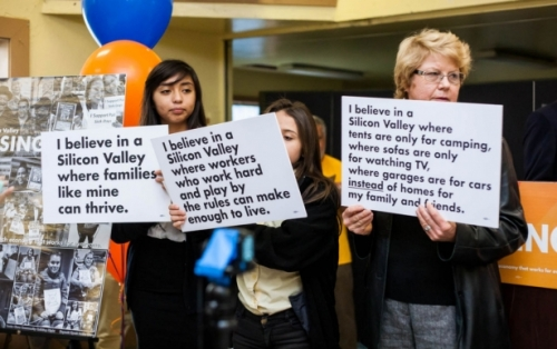 Supporters of Silicon Valley Rising hold signs at the coalition's launch.