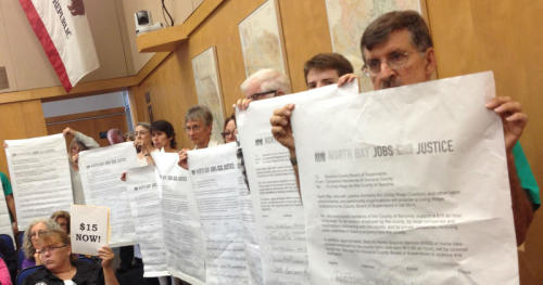 Living Wage advocates unfurled enlarged copies of petitions calling for a new $15 per hour rate as the 2200 regular size petitions were presented to County Supervisors Tuesday afternoon. (Photo credit: Bruce Robinsoon, KRCB)