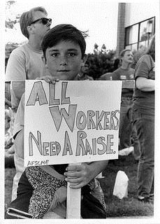 "Child holds sign saying, ""All workers need a raise"""